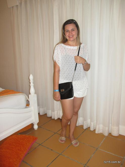 Emanuela veste blusa branca com bolinhas pretas, shorts branco, rasteirinha branca e bolsa preta