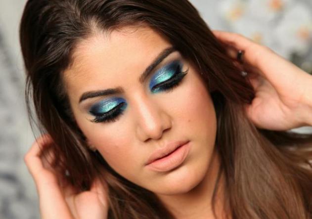 Olhos maquiados com sombra verde na pálpebra móvel, concavo marcado com azul e V em preto