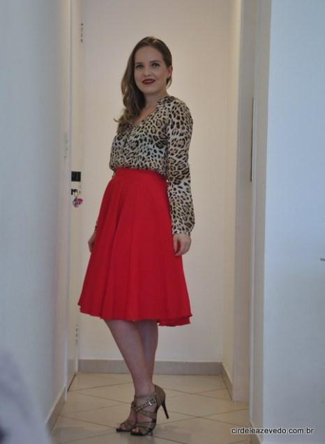 Eu usando saia midi vermelha e camisa de manga comprida com estampa de bicho