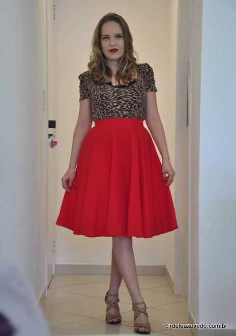 Eu usando saia midi vermelha e blusa de manguinhas bufantes com estampa de bicho e detalhe de renda preto no busto