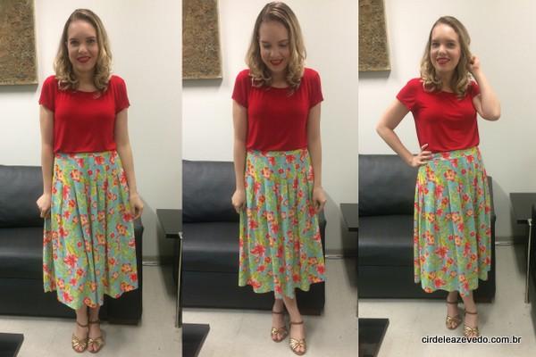 eu suando blusa de mangas curtas vermelha, tecido malha, com saia midi floral de fundo verde e sandália nude