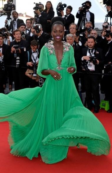 Lupita veste vestido longo verde vaporoso com detalhes nos ombros