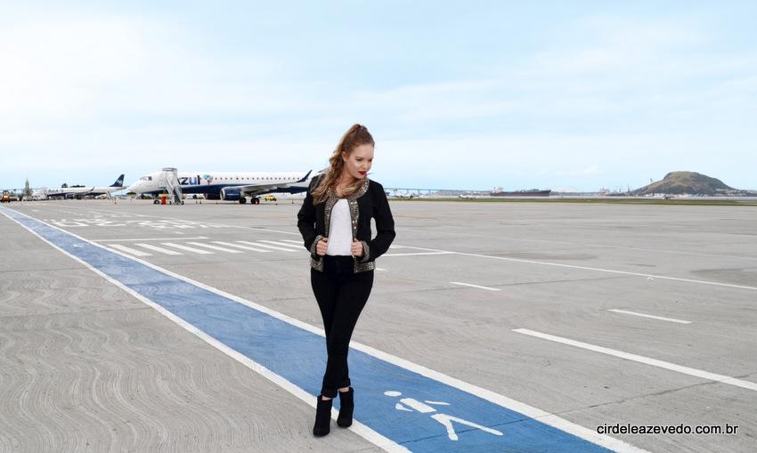 Eu na pista do aeroporto Santos Dumont usando calça, casaco e bota pretos e regata branca