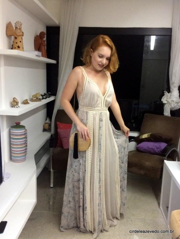 vestido longo estampado, com detalhes em entremeios, e a bolsa em madeira com tassel