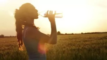 stock-footage-hot-summer-sunset-woman-drinking-water-tired-runner