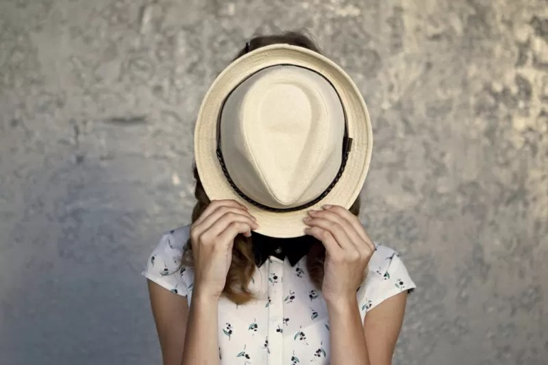 timidezza dietro ad un cappello