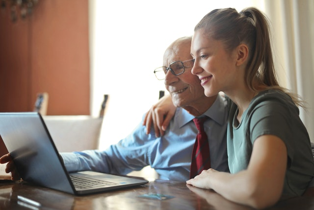 young positive woman helping senior man using laptop 3823489
