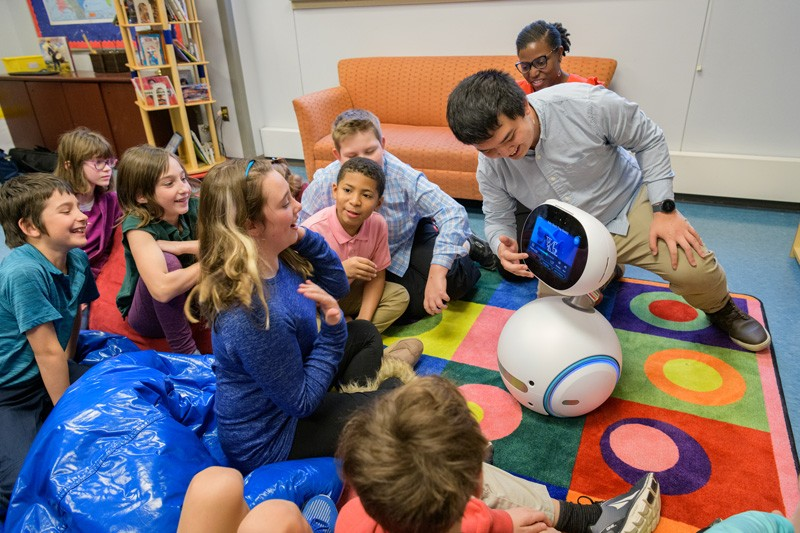 Fifth graders at The College School, located on UD's Newark Campus, watch Zenbo the social robot, while doctoral student Yan-Ming Chiou guides the conversation and Prof. Tia Barnes looks on.