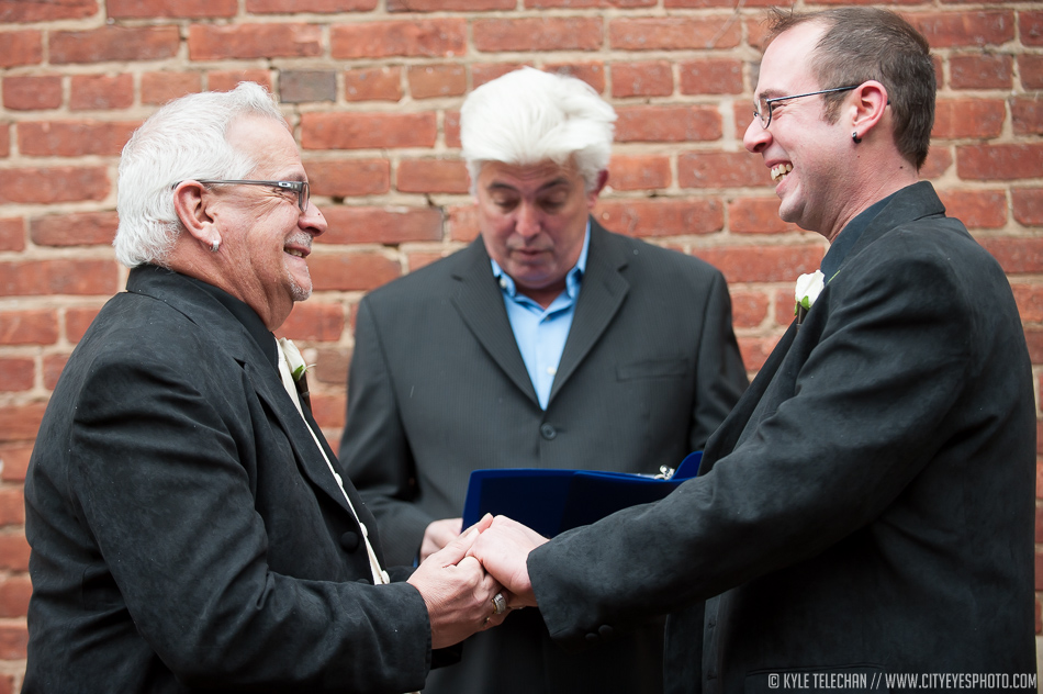 Partners Bobby, on left, and Nicky Stavitzke-Samar smile at each other as Jim Bilow pronounces them married during their wedding ceremony in downtown Crown Point on Friday.