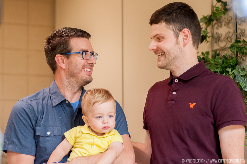 Newlywed couple Eric Evans, holding son Sawyer, on left, and Adam White look at each other on Wednesday after becoming the first gay couple to wed in Lake County.