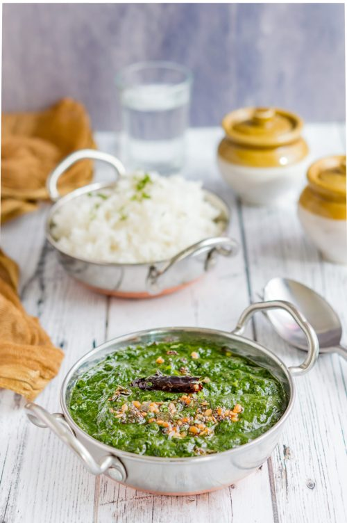 Mashed spinach displayed on an Indian kadai with a bowl of rice on the side.