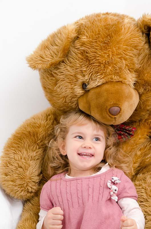 Portrait d'une petite fille de 2 ans dans les bras d'un ours en peluche