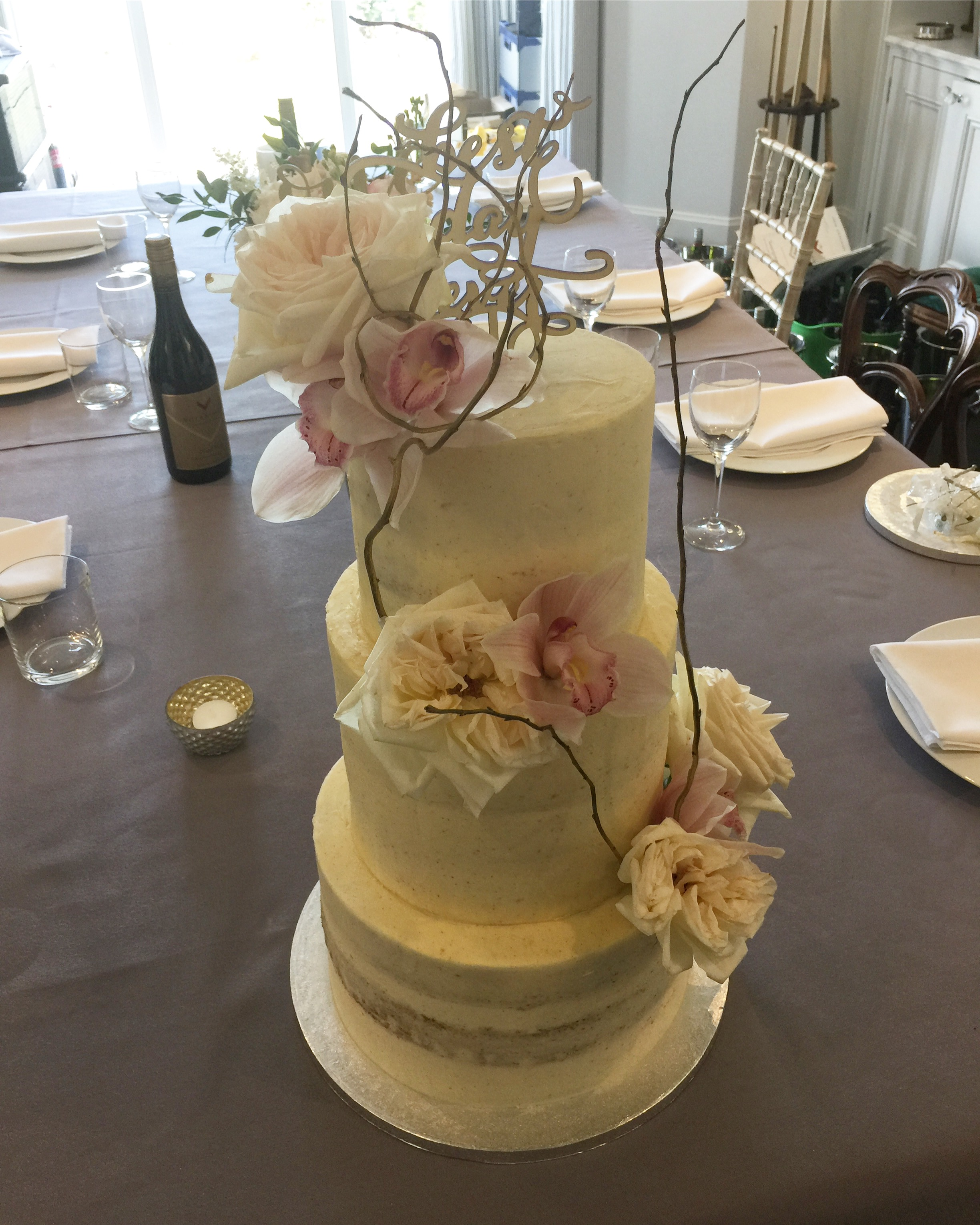 Semi naked wedding cake with fresh flowers and twigs