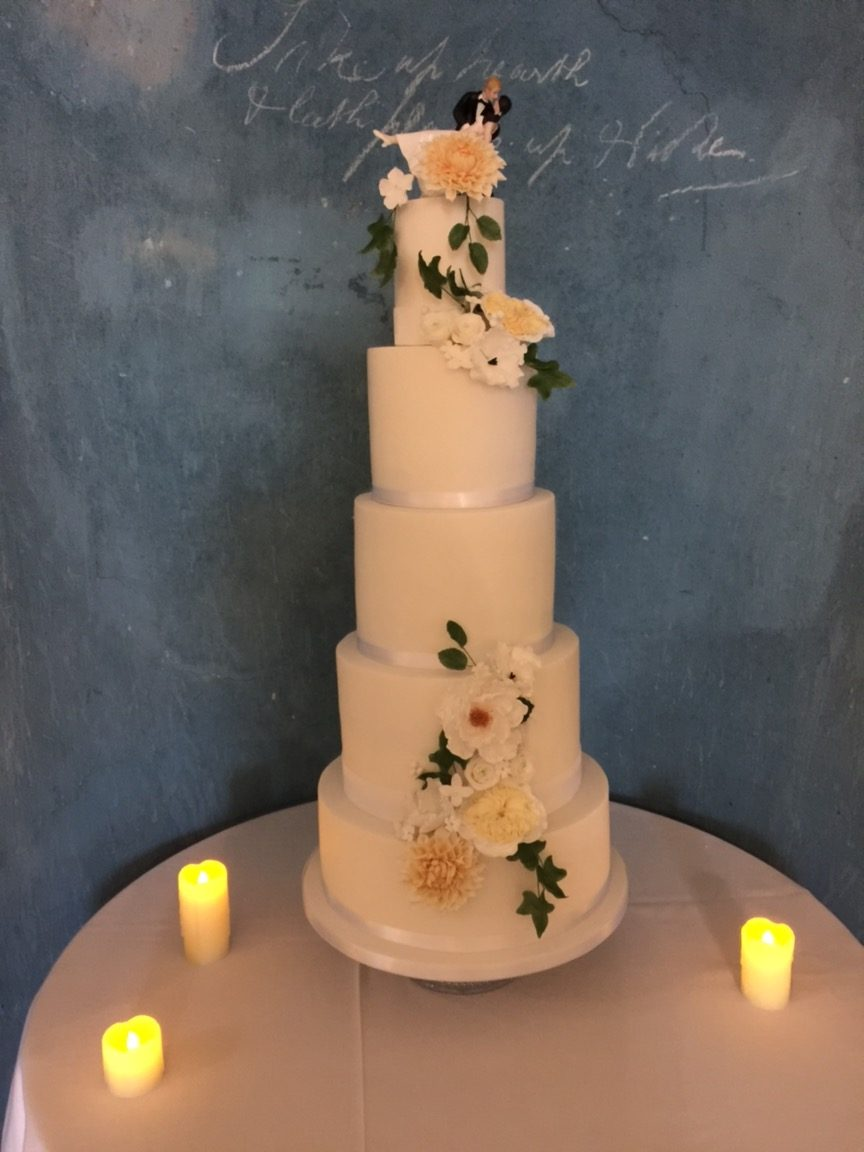 5 tier white wedding cake with sugar flowers