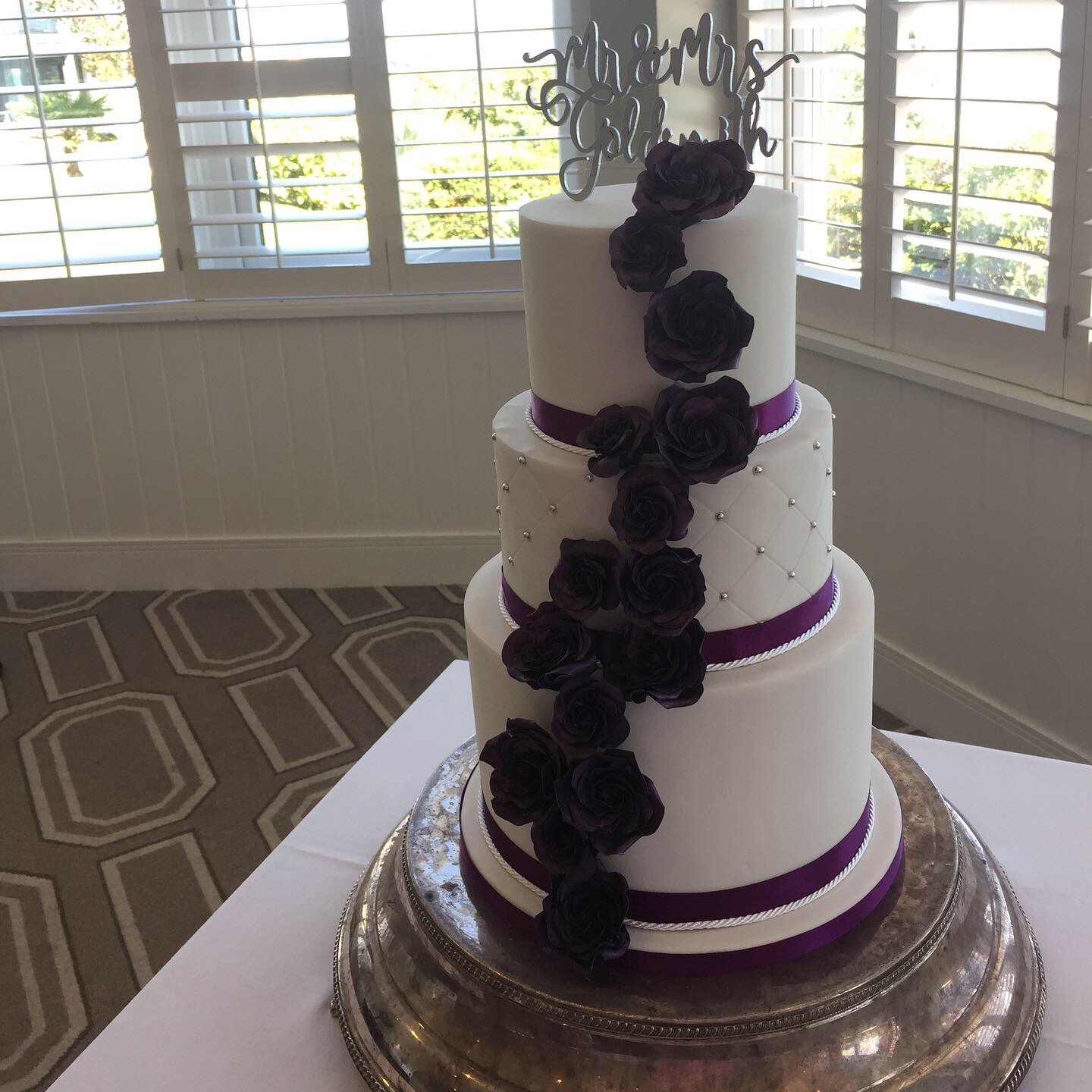 white wedding cake with purple sugar roses