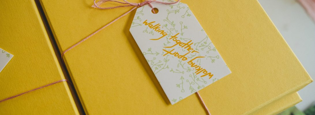 A stack of yellow gift boxes, tied with pink thread and a gift tag that reads 'Walking together, walking apart'