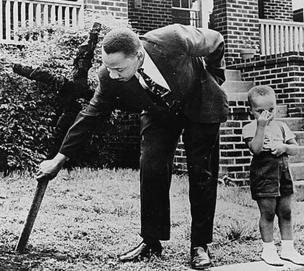 13. Martin Luther King e seu filho removendo uma cruz queimada por membros do KKK em frente a sua casa em 1960.