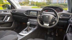 Peugeot 308 interior shot showing the large touchscreen and high mounted instrument panel. The steering wheel is smaller than you'd expect.