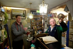 Publican/Hardware shop owner and wool merchant Colman Keane and his son Peter with some of their old ledgers and the hoop that WB Yeats used tie his horse to, in the family's premises at Gort.  Photograph by John Kelly.