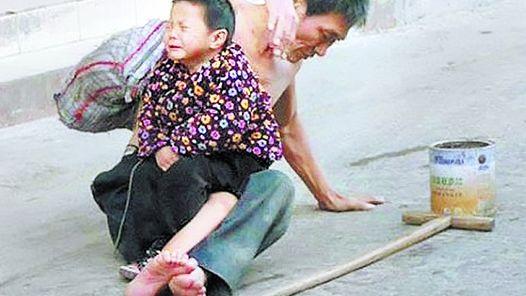 EN LA CALLE. UN PADRE Y SU NIÑO MENDIGAN EN UNA CIUDAD CHINA.