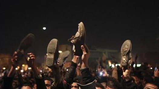 RECLAMO. Manifestantes egipcios sostienen sus zapatos, tras la intervención por televisión del presidente egipcio, Hosni Mubarak. (AP)