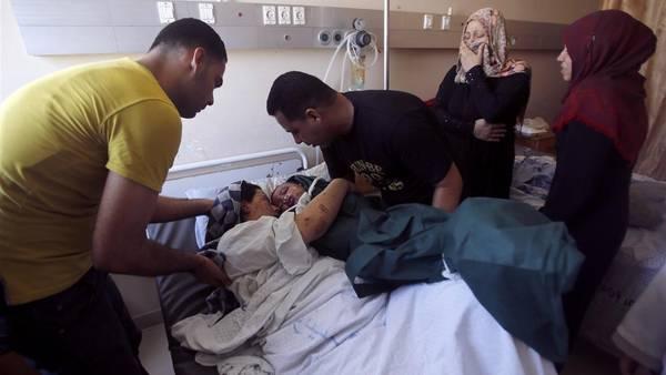Un padre palestino acerca a su esposa el cuerpo de su hijo de tres años, muerto durante los bombardeos en Gaza, en el hospital de Shifa. (AP)