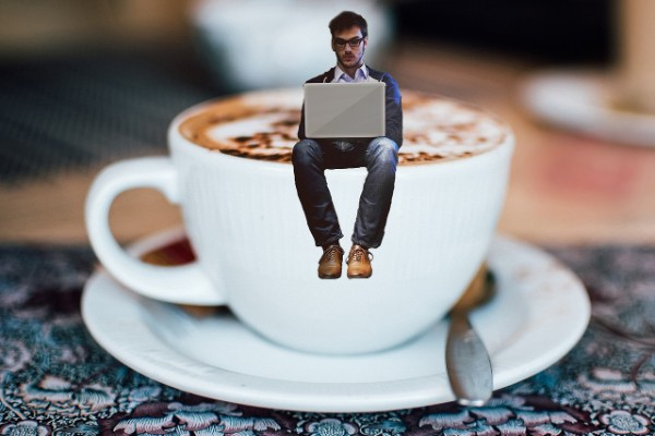 Man reading in a coffee cup