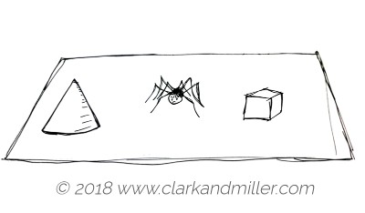 A cone, a spider and a cube on a table