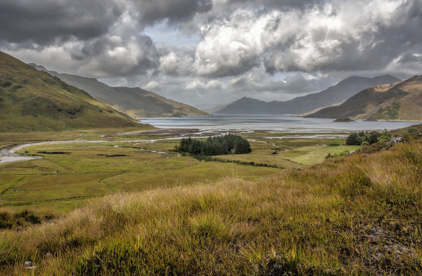 The Scottish Highlands with grass, a lake, distant mountains and low-lying dark clouds