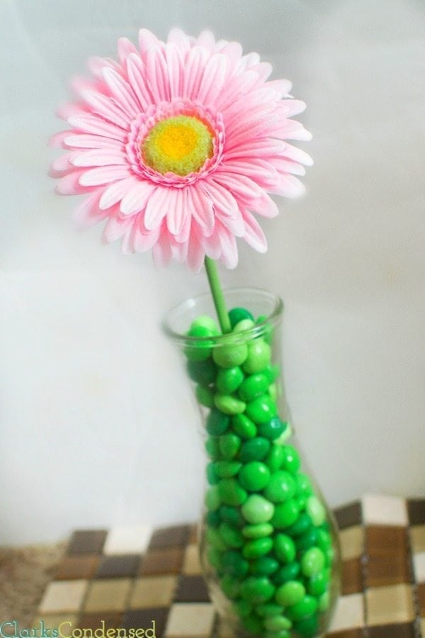 Looking for a simple wedding centerpiece? This M&M flower vase takes minutes to put together and is easily customizable. This post also has five other fun ways to use M&Ms at your wedding!