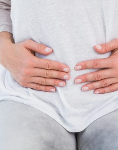 woman holding her bloated stomach