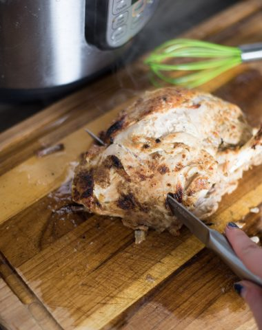 A piece of turkey breast sitting on top of a wooden cutting board