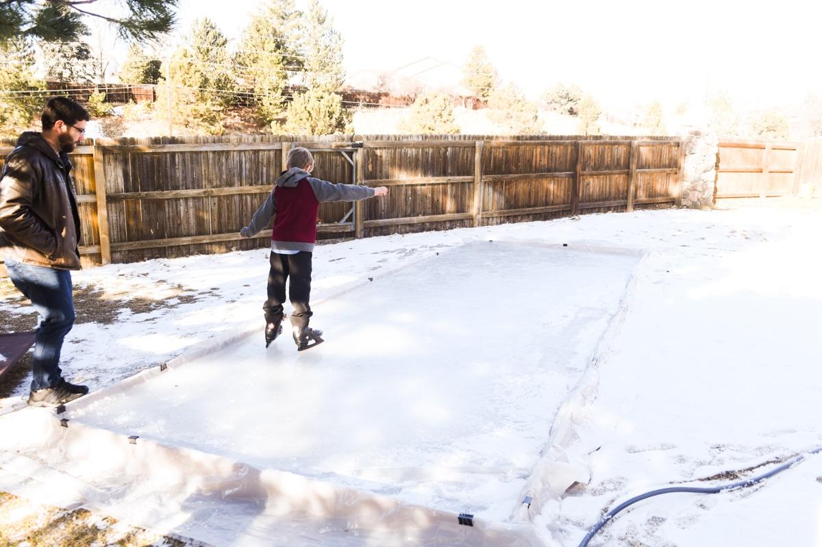 child ice skating in backyard ice rink