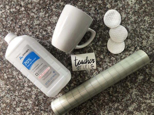 supplies: mug, vinyl design, transfer tape, rubbing alcohol, and cotton rounds