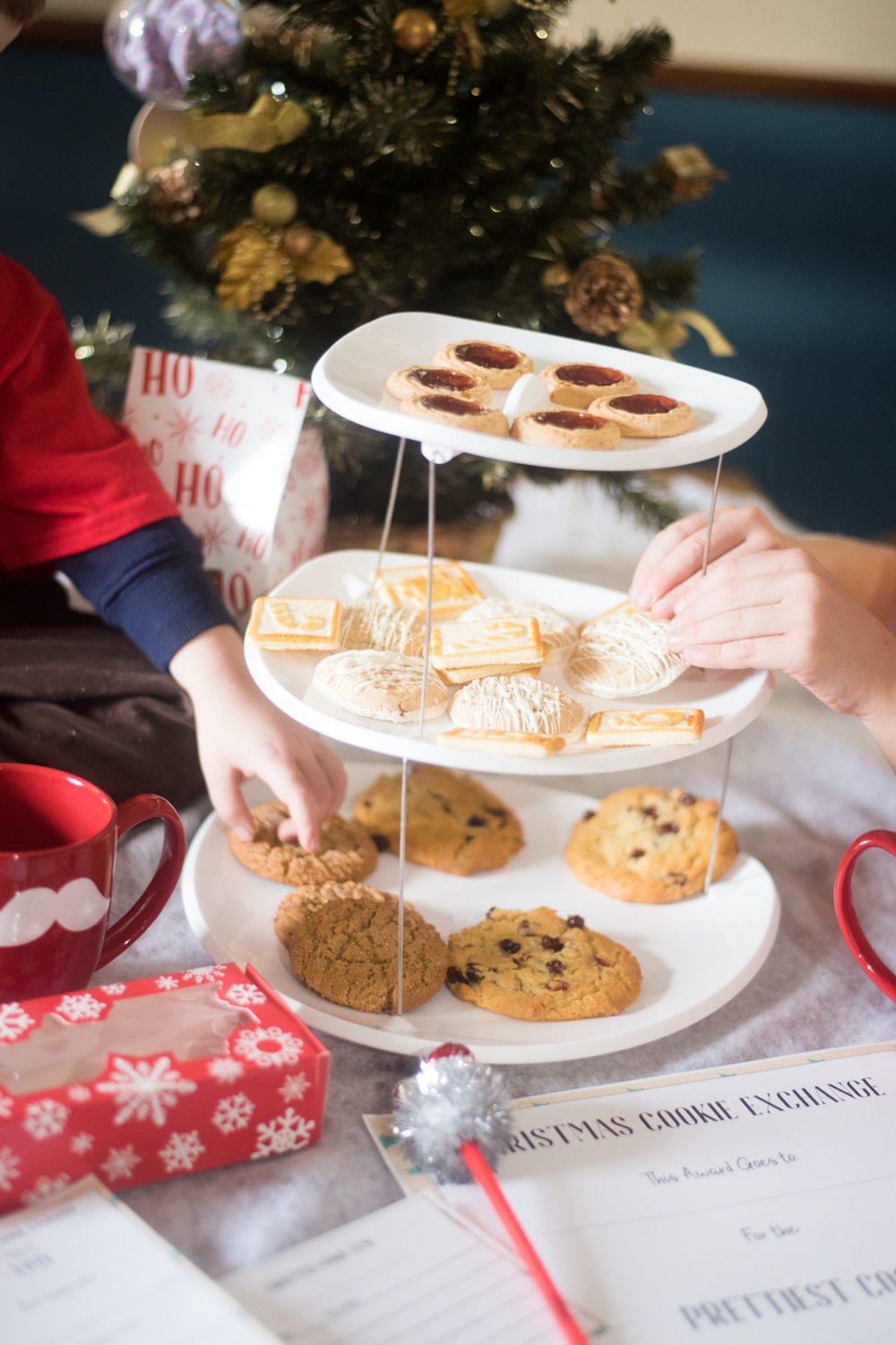 A woman sitting at a table with a plate of food, with Christmas cookie