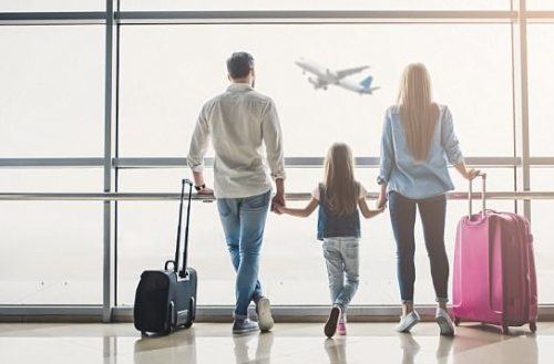 Family in airport. Attractive young woman, handsome man and their cute little daughter are ready for traveling! Happy family concept.; Shutterstock ID 1033801318; Purchase Order: -