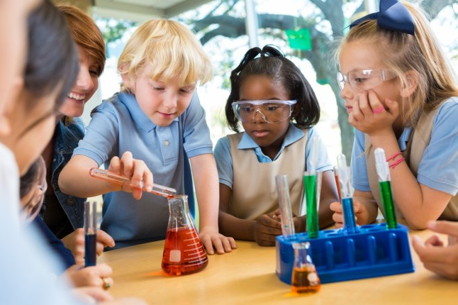 Elementary school students doing chemistry science experiment in class