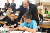 McCaffrey Middle School Principal Ron Rammer listens into the conversation of Martin Bastida and Thomas Leitner (left to right) elbow partners explaining the model of the elliptical orbit of the Earth around the sun.