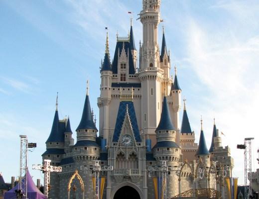 castelo estilo medieval em pedra com varias torres pontiagudas com os cumes em azul. todas as torres tem janelas pequenas. no centro do castelo, acima do grande portal em arco da entra, existe um relógio. É o castelo da Cinderela, personagem querida pelas crianças e fica na Disney World