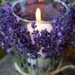 vela branca, tipo de 7 dias, grossa, colocada em porta vela de cristal envolvido em flores de lavanda delicadamente amarradas com fios de ráfia.Ao centro da mesa o efeito é delicado e luminoso.
