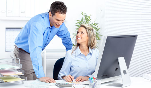 mulher loira bonita, vestida com camisa azul clara, sentada à frente do computador mostra papéis de trabalho para um homem. Percebemos que eles estão em um escritório e tendo uma conversa agradável