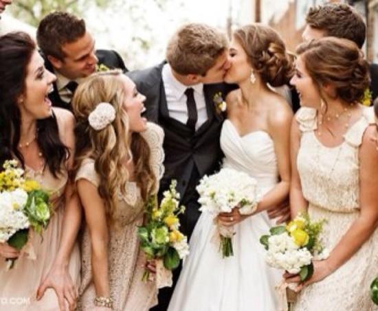 casal de noivos se beijando cercados por 3 madrinhas e dois padrinhos que observam a cena com alegria.
