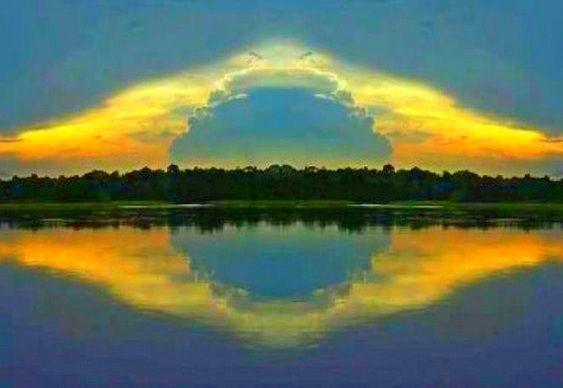 Imagem do Rio Amazonas, num entardecer, nuvens amarelas junto a mata em forma do losango da bandeira. A imagem está espelhada nas águas do rio. Exatamente a bandeira nacional.