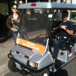 Claudia Matarazzo, usando jeans, blusa colorida, e casaco marrom, está junto ao carro elétrico da Rede Globo, que levará para os estúdios do programa da Fátima Bernardes.