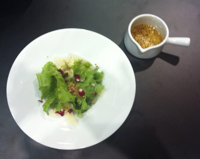 Prato fundo de porcelana branca tamanho médio em relação ao outro mostrado acima. Dentro, folhas de salada com frutas vermelhas e ao lado uma molheira pequena de louça branca com molho de azeite e mostarda