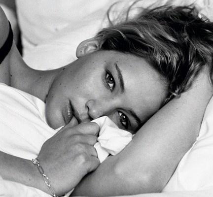 A atriz Jennifer Lawrence, em foto preta e branca, deitada numa cama, seu rosto apoiado no braço esquerdo e o outro segura lençóis, cabelos despenteados,