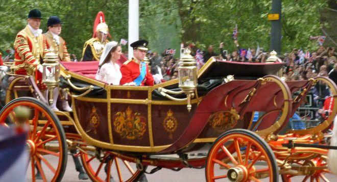 Imagem dos noivos Kate Middleton e Príncipe William do Reino Unido, ela vestida de noiva branco e véu e ele fardado com uniforme de gala , vermelho com uma faixa azul do ombro esquerdo para a direita do corpo, usa uma cobertura militar preta, , estão numa carroagem da Corte Britanica , puxada por cavalos e atras da carroagem dois militares da cavalaria real.