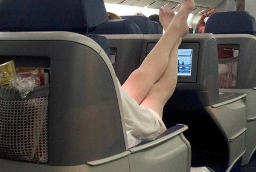 Passageira de um avião, vestindo provavelmente um short ou bermuda, durante o vôo, estica suas pernas e as repousa na cabeceira da poltrona da frente