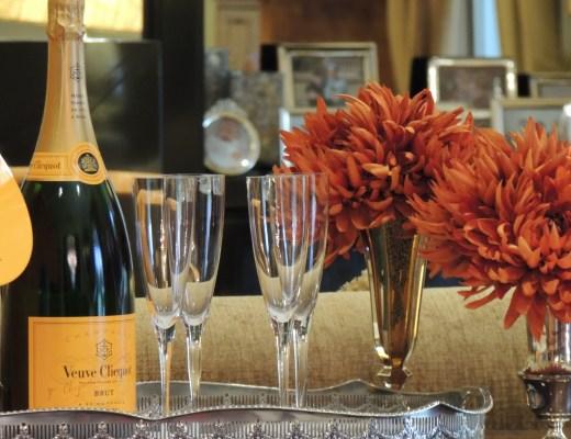 Bandeja em prata que está sobre uma mesa, que contem quatro taças de champanhe, ao centro, a esquerda uma garrafa de champanhe Veuve Clicquot, na cor verde, fechada onde temos o famoso rótulo da marca, na cor dourada, e a direita temos dois pequenos vasos, um de vidro e outro em prata, com flores na cor laranja escura, quase ferrugem. ao fundo temos alguns porta-retratos.