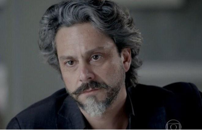 """Ator Alexandre Nero, em foto de divulgação, apenas o rosto de frente, com seus cabelos grisalhos, barba e bigode da mesma cor, e em função do seu personagem na novela """"Império"""", ele veste camisa e paletó na cor preta."""